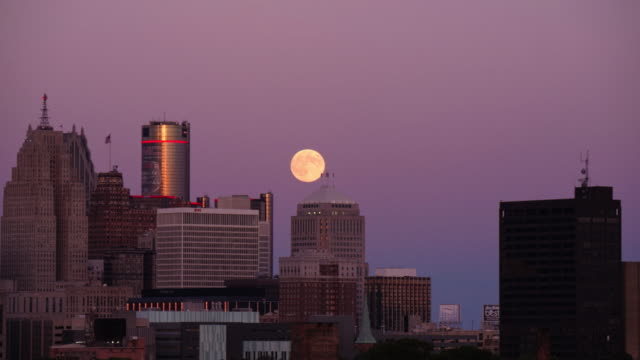 full moon rising behind detroit skyline. day to night time lapse - spoonfilm stock-videos und b-roll-filmmaterial