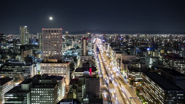 vídeos de stock, filmes e b-roll de tl, ws full moon rising over central osaka at night / osaka, japan - time lapse de trânsito