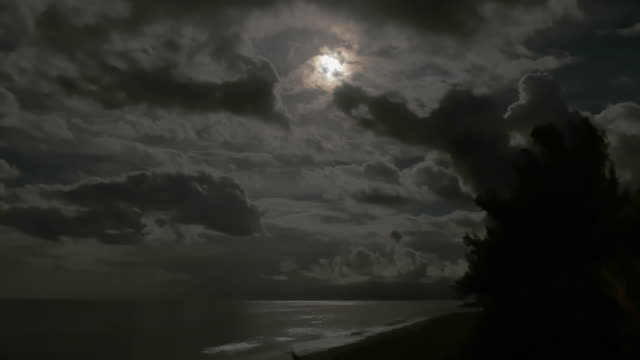 full moon rising with dramatic clouds and reflections on the caribbean sea – wide shot - 色が変わる点の映像素材/bロール