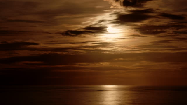 full moon rising with dramatic clouds and reflections on the caribbean sea - 色が変わる点の映像素材/bロール
