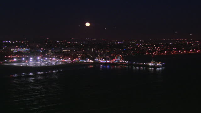 aerial full moon sitting over the pacific park ferris wheel illuminated and spinning after dark / santa monica, california united states - santa monica pier stock videos & royalty-free footage