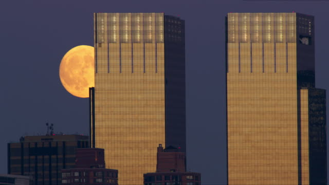 Full moon slowly rises behind the Time Warner building
