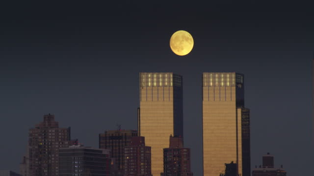 full moon slowly rises behind the time warner building - time warner center stock videos & royalty-free footage