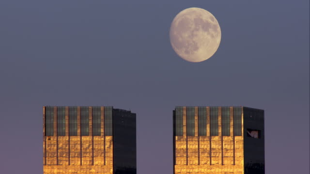 Full moon slowly rising above the tops of twin skyscrapers against a clear sky in New York City