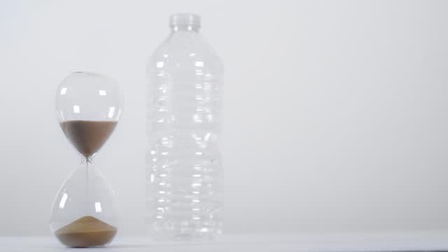vídeos de stock e filmes b-roll de full sand timer next to plastic bottle on white background - utilização única