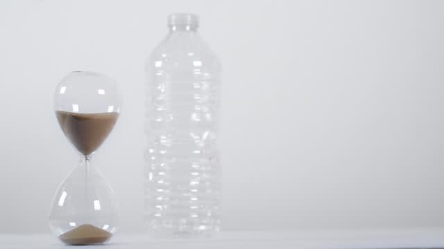 vídeos de stock e filmes b-roll de full sand timer next to plastic bottle - utilização única