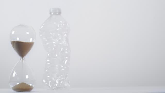 vídeos de stock e filmes b-roll de full sand timer with crushed plastic bottle 2 - utilização única