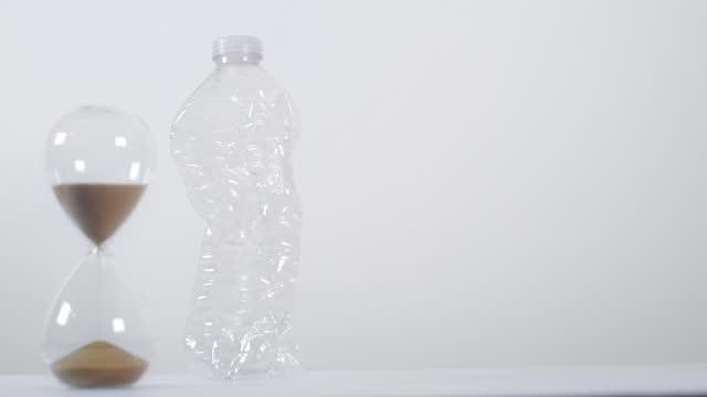vídeos de stock e filmes b-roll de full sand timer with crushed plastic bottle - utilização única