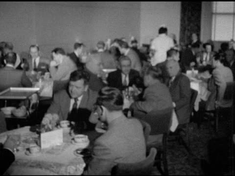 stockvideo's en b-roll-footage met full service dining room w/ businessmen sitting at tables, some plates being cleared, waiter walking to table, captain in tuxedo delivering menus,... - dining room