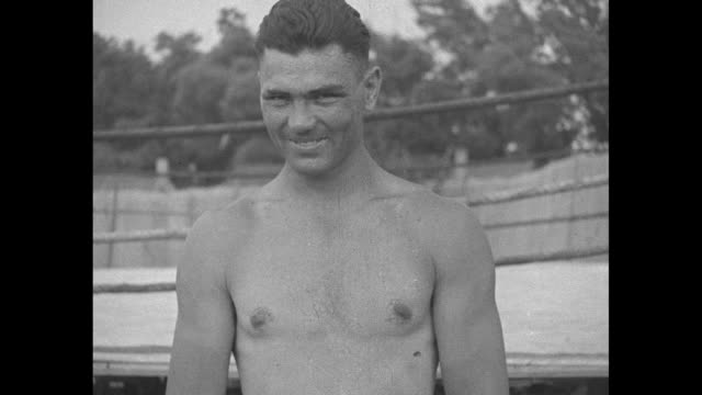 Full shot as boxer Jack Dempsey smiles / close shot Dempsey smiles and speaks / close shot Dempsey shows off arm muscle / Dempsey punches ring ropes...