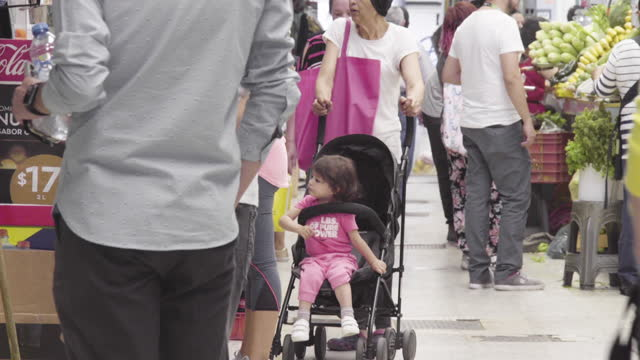 full shot. customers wait at a grocery stand. people walking toward the camera. full shot of a little girl seated in her stroller - black hair stock videos & royalty-free footage