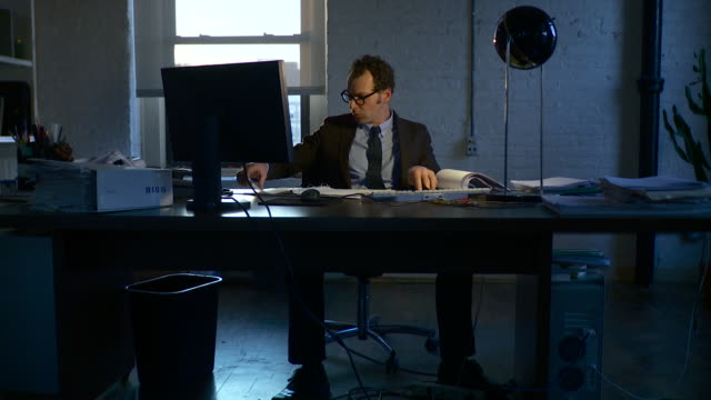 full shot. dolly to the left around man sitting at desk, reading paperwork, working late into the night. - abbigliamento da lavoro formale video stock e b–roll