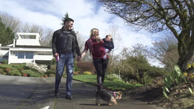 Full shot of a family walking a dog