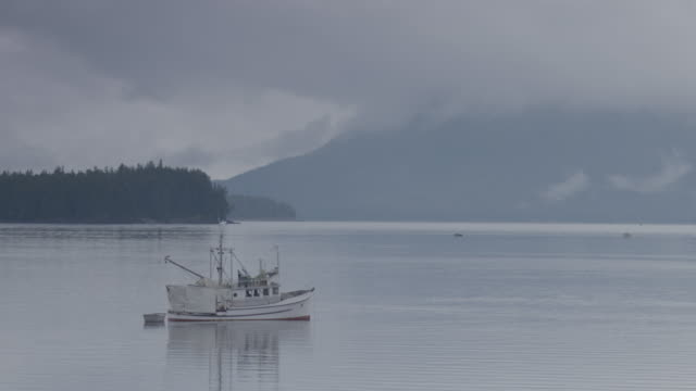 Full shot of a moored fishing boat with mountains in the background