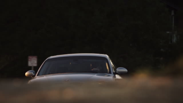 Full shot of a silver BMW 2009 135i Coupe driving past on a ridge at sunset.