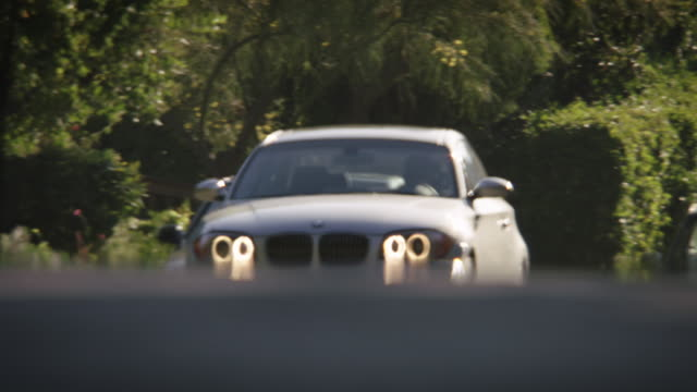 Full shot of a silver BMW 2009 135i Coupe driving toward the camera then turning a corner in a residential neighborhood.