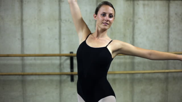 full shot of a woman practicing a beautiful dance with large, elegant arm motion. - gymnastikanzug stock-videos und b-roll-filmmaterial