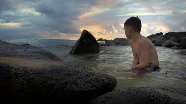 full shot of boy playing in the rocks and tide - pantaloncino da bagno video stock e b–roll