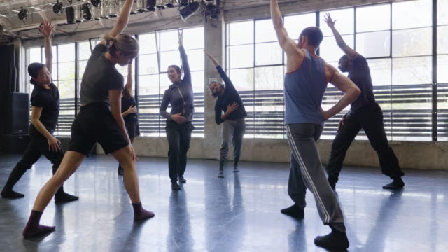 vidéos et rushes de full shot of female trainer and dance troupe stretching and warming up together - studio de danse