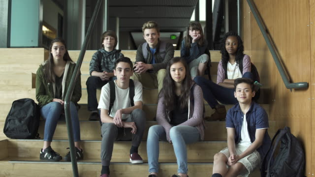 full shot of high school students sitting on stairs - schoolboy stock videos and b-roll footage