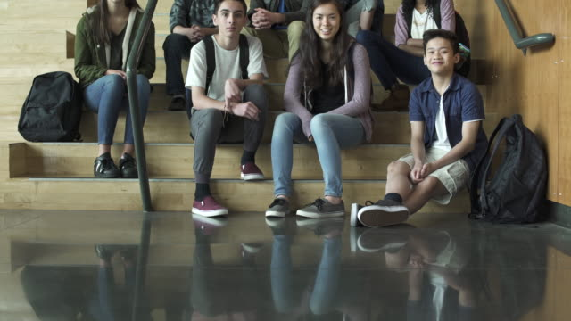 Full shot  of high school students sitting on stairs