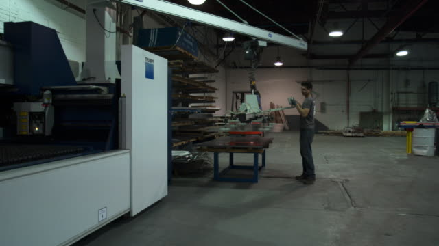 full shot of man carrying a piece of sheet metal over to laser machine. - sheet metal stock videos and b-roll footage
