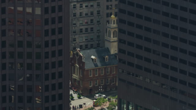 full shot of the old state house appearing from behind a high-rise building - boston massachusetts stock videos & royalty-free footage