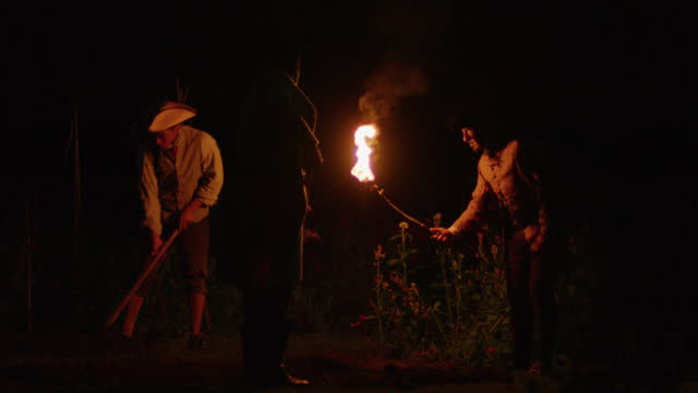 stockvideo's en b-roll-footage met full shot of two men digging a grave while another one holding a torch at night - men