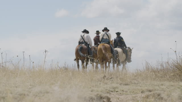 vidéos et rushes de full shot of the soldiers of the us cavalry moving away from the camera - grandes plaines américaines