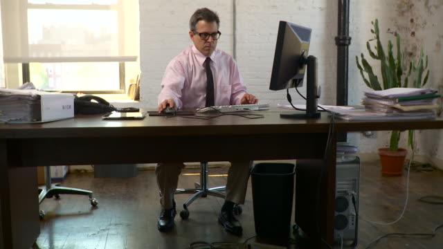 full shot. slow dolly to the right. man works at a computer at his desk. - abbigliamento da lavoro formale video stock e b–roll