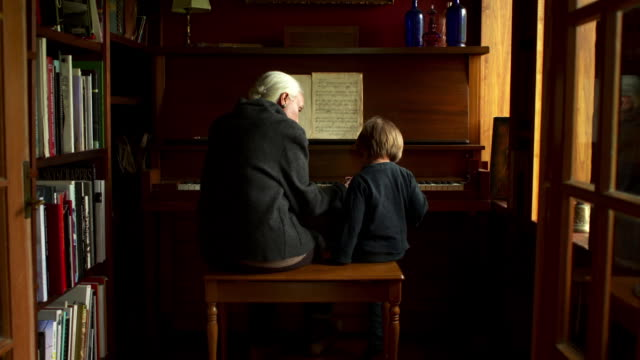 full shot. slow push in on grandmother and grandson playing the piano. - grandchild stock videos & royalty-free footage