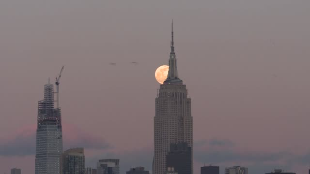 full snow moon rises over the empire state building in new york city, united states on february 8, 2020. - empire state building stock videos & royalty-free footage