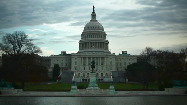A full, static shot of the United States Capitol Dome Building against a cloudy sky.