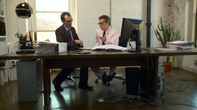 full two shot. dolly to the right around two men sitting at one desk as they talk to one another. - skjorta och slips bildbanksvideor och videomaterial från bakom kulisserna