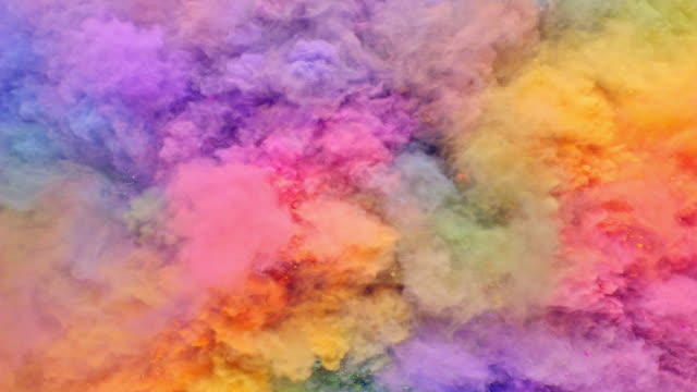 fullframe overhead view of a surface filled with multi pastel colored powder blasting towards camera and bouncing smoky texture in close up and super slow motion - カラフル点の映像素材/bロール