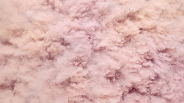 fullframe overheadview of a surface filled with rose gold blusher powder blasting towards camera and bouncing smoky texture in close up and super slow motion - アイシャドウ点の映像素材/bロール