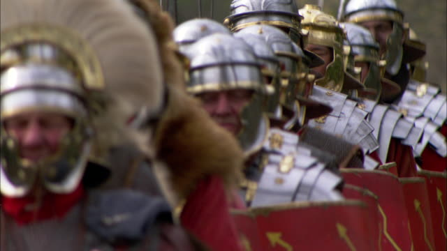 vídeos de stock, filmes e b-roll de fully armored roman soldiers march in single file. - reconstituição histórica