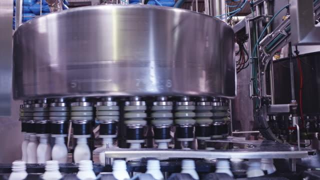stockvideo's en b-roll-footage met volledig geautomatiseerde hoge snelheid melk bottelen plant - productielijn werker