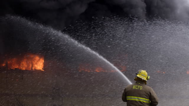 A fully engulfed structure fire belches black smoke as firefighters shoot streams of water from three directions