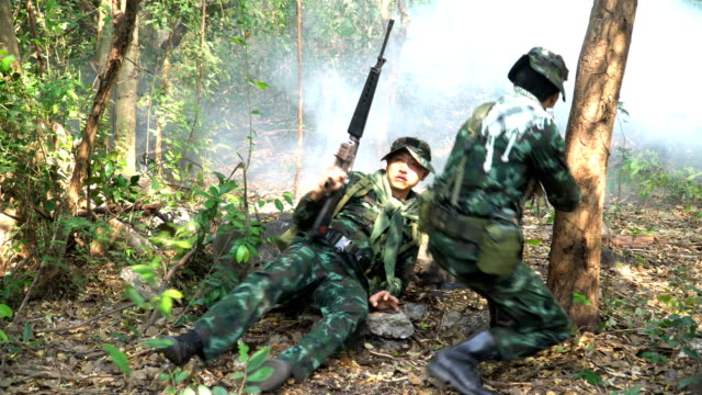 Fully Equipped and Armed Soldier looking the enemy before patrolling to tropical forest