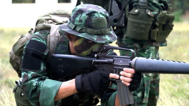 vidéos et rushes de entièrement équipé et visage-camouflage militaire visent à tirer avec son geste - arme à feu