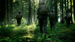 Fully Equipped Soldiers Wearing Camouflage Uniform Attacking Enemy, Rifles Ready to Shoot. Military Operation in Action, Squad Running in Formation Through Dense Smokey Forest. Back View Slow Motion Footage.