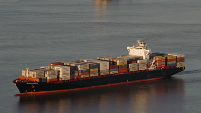 AERIAL Fully loaded large cargo ship sailing in the morning sun