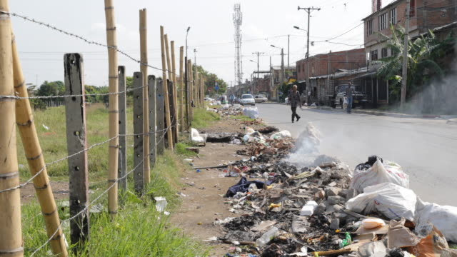 fuming trash lying on the side of a road at el vertel a neighborhood with high criminality rate - america del sud video stock e b–roll