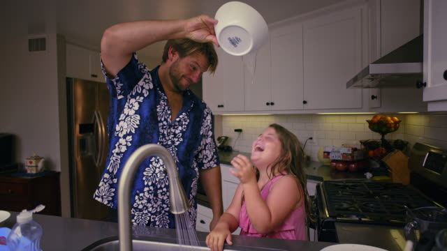 fun and games father pours water on his daughter as they clean dishes together. med - routine stock-videos und b-roll-filmmaterial