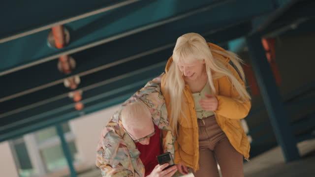 spaß und moderne albino-freunde, spaß zusammen beim anschauen interessanter inhalte im internet - content stock-videos und b-roll-filmmaterial
