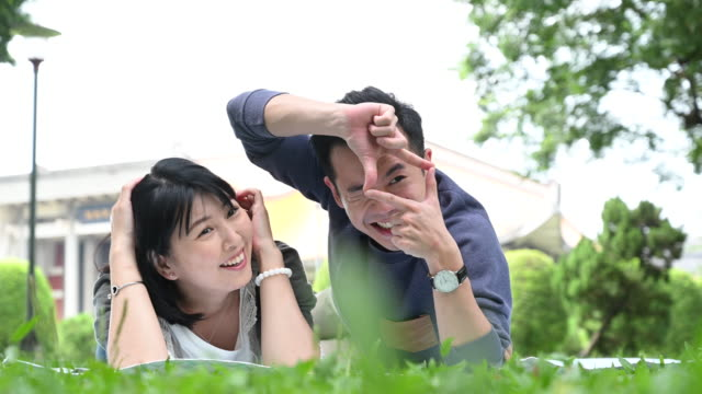fun chinese couple making finger frames in park - mid adult couple stock videos & royalty-free footage