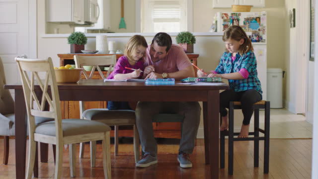 WS. Fun dad laughs and draws with his youngest daughter while older sister works on homework.