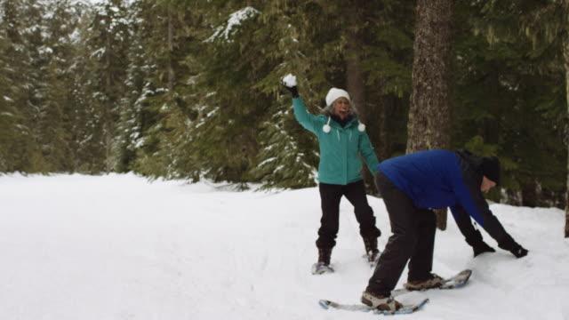 Fun elderly couple having a snowball fight