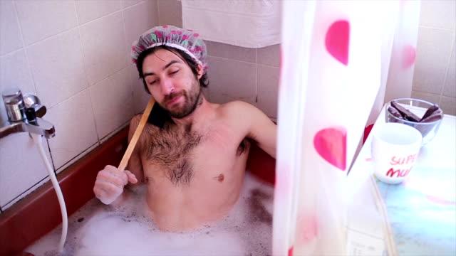 vídeos y material grabado en eventos de stock de diversión guy le gusta en la bañera-cámara lenta - ducha